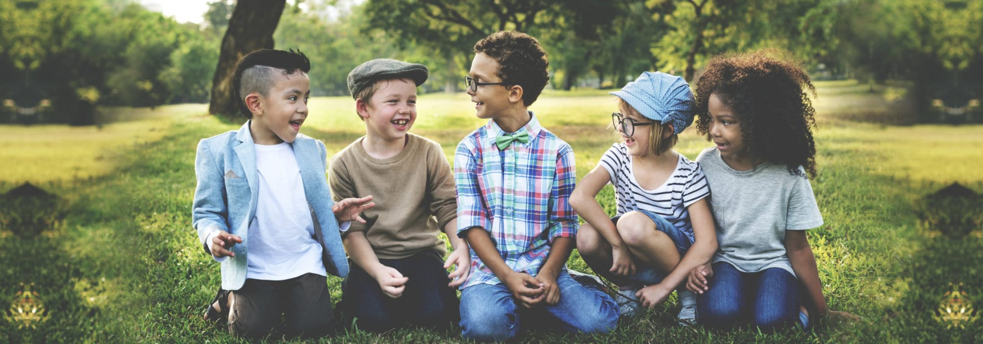 Group of kids look happy sitting on the grass