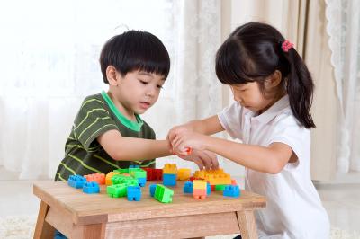 Asian kids piling up building blocks