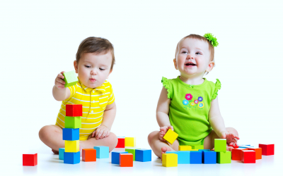 Two adorable babies kids playing with educational toys