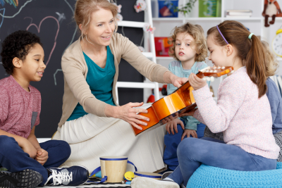 Little preschool girl holding teacher's guitar on music lesson