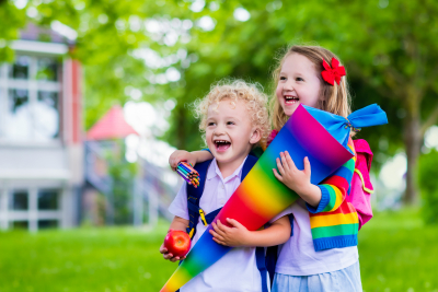 Boy and girl holding traditional candy cone on the first school day